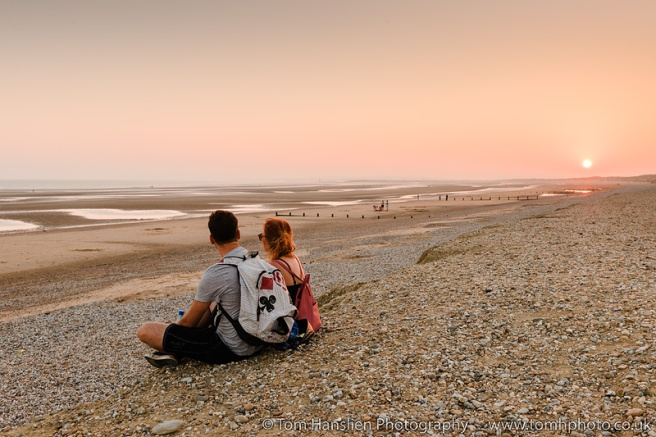 A couple enjoying the sunset on Camber Sands Beach.